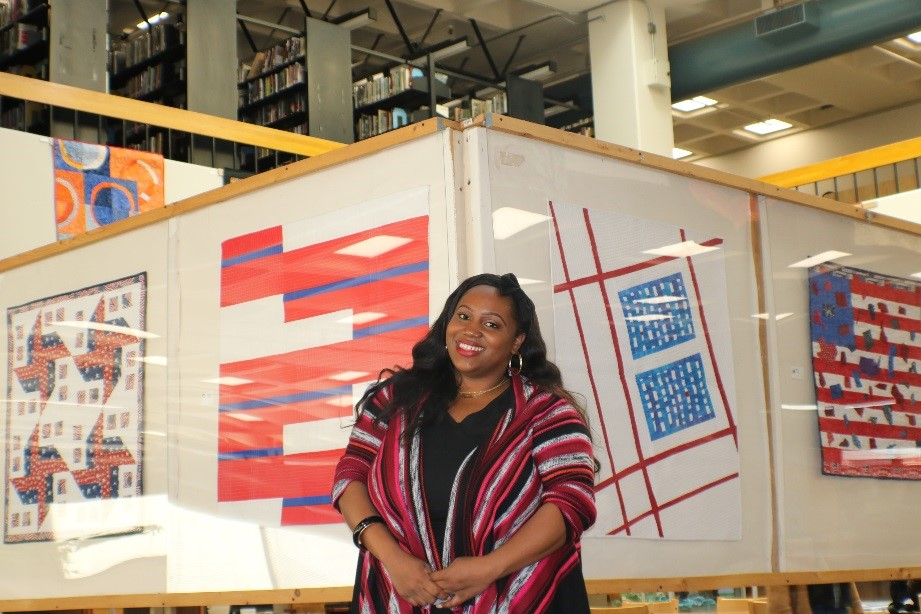 Dominique Dozier stands in front of colorful quilt display at Laney Library